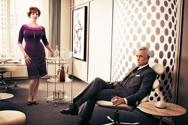 <p>Joan Holloway (Christina Hendricks) with the bar cart in Mad Men, with Roger Sterling (John Slattery)</p>