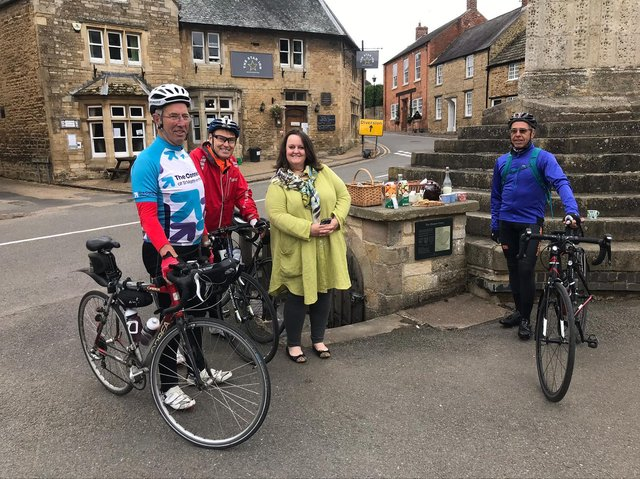 Challenge riders Keith Wright (left), Iain Dibble (centre) and Henry Laprun next to the cross in Geddington with Lisa Wilkinson from the village who provided some refreshments