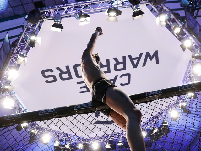 Jordan Vucenic celebrates at the top of the cage after he became the Cage Warriors featherweight champion. Pictures by Dolly Clew (www.dollyclew.com)
