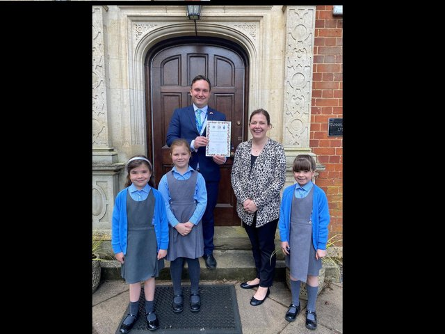 Headteacher Mark Thomas, music teacher Carly Palmer and some of the pupils with the Rose of Northamptonshire Award