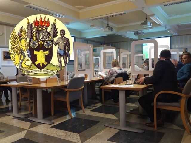 The council meeting last night and, inset, the old coat of arms.