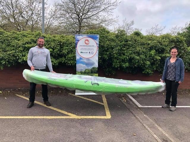 Nick receives his kayak from Corinne Muir