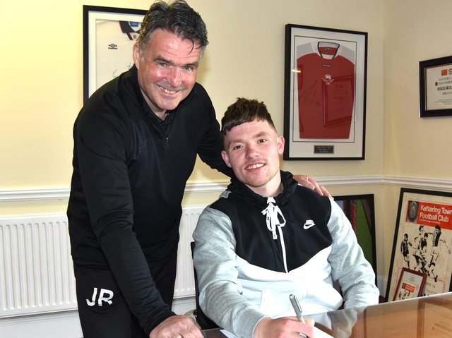 Jordon Crawford, who left Corby Town last week, puts the finishing touches to his move to Kettering Town alongside Poppies assistant-manager John Ramshaw. Picture courtesy of Paul Cooke/Poppies Media