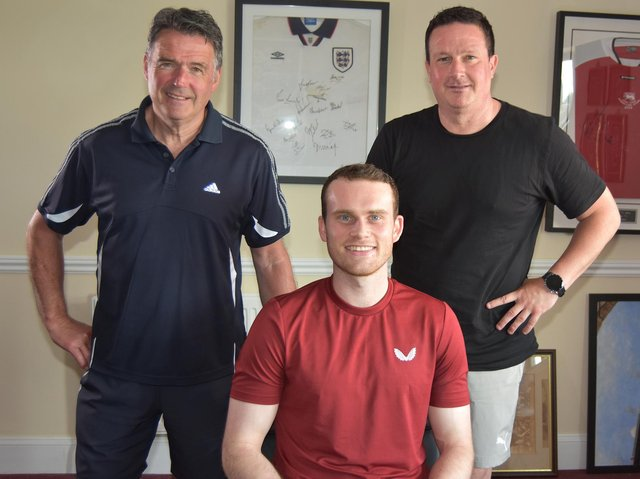 Central defender Chris Smith signed for Kettering Town under the watchful eyes of manager Paul Cox and assistant-boss John Ramshaw. Picture courtesy of Poppies Media