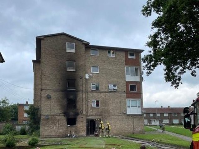 The block of flats shows smoke damage on the outside