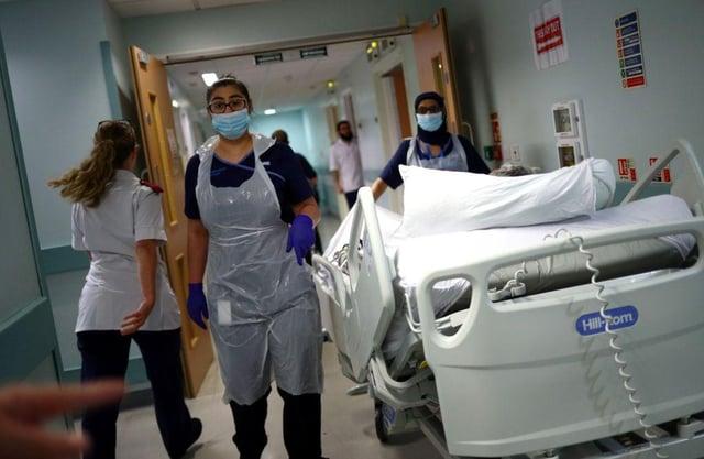 Medical staff transfer a patient along a corridor at the Royal Blackburn Teaching Hospital (Photo: HANNAH MCKAY/POOL/AFP via Getty Images)