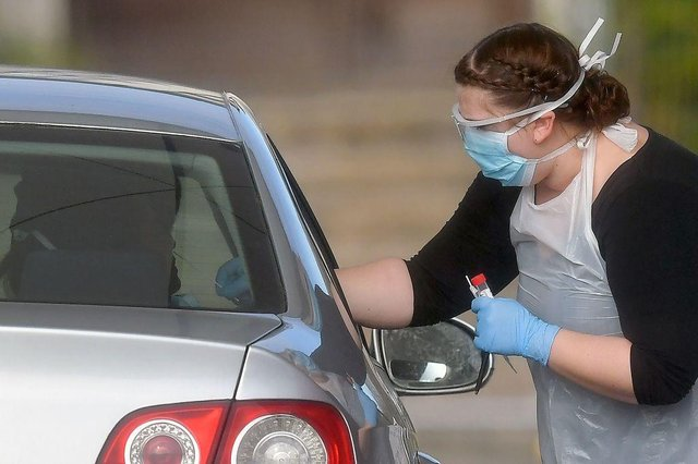 A worker in PPE including gloves, a face mask, eye protection and an apron, swabs an NHS worker at a drive-in facility to set up to test for the novel coronavirus COVID-19, in the car park of Chessington World of Adventures (Photo: BEN STANSALL/AFP via Getty Images)